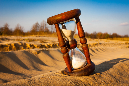 old hourglass on sand in desert Stock Photo