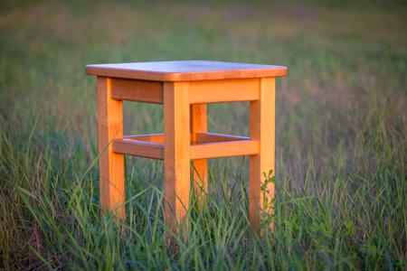 Taburete de madera abstracto en prado verde Foto de archivo