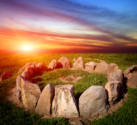 stone circle in grass on sunset background