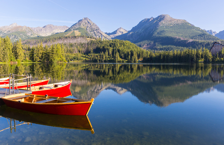 wooden boats on the pier in a mountain lake, Tatras in Slovakia