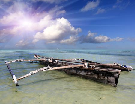 Wooden old fishing boat in turquoise ocean water in low tide time, Zanzibar Archivio Fotografico
