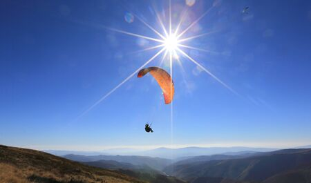 paraglider fly in mountains in sunny day