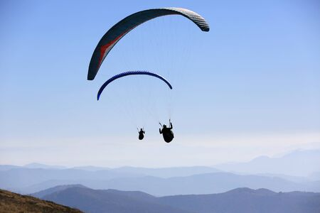 flying paragliders in air over mountains 版權商用圖片