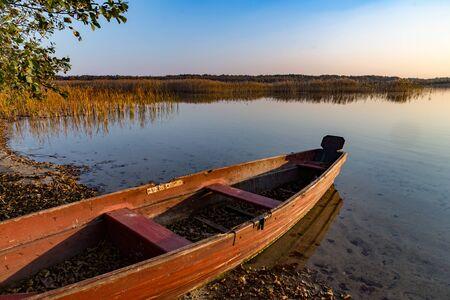 altes Holzboot am See. Abendlandschaft, Herbst