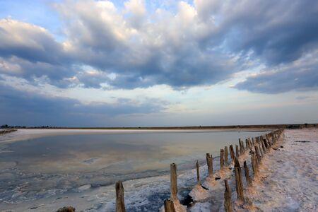 Nice sky over slat surface on lake near Azov Sea in Ukraine. Old wood in salt Stock Photo