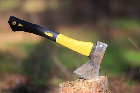 abstract axe with yellow handle grip in wooden chop