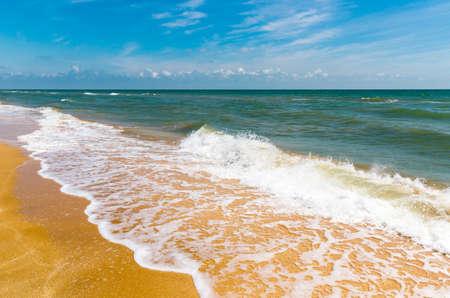 Summer scene on sea shore. Sea foam on yellow sand Standard-Bild