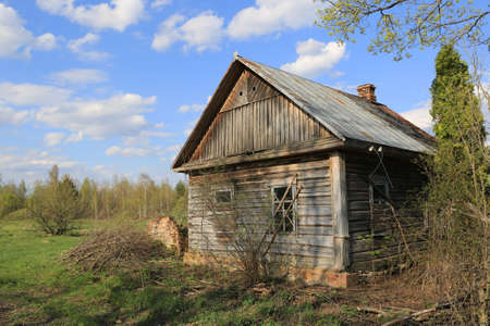 old abandoned wooden house on the edge of a green meadow on a spring day