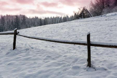 wooden fence on winter meadow in mountains Standard-Bild