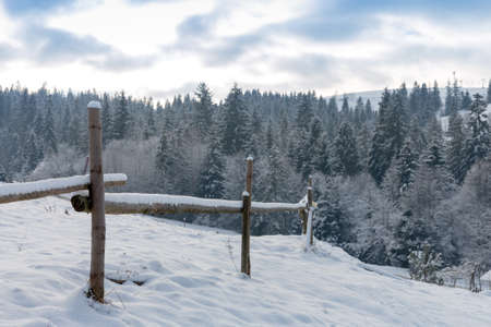 Winter landscape with wooden fence on meadow border in mountains