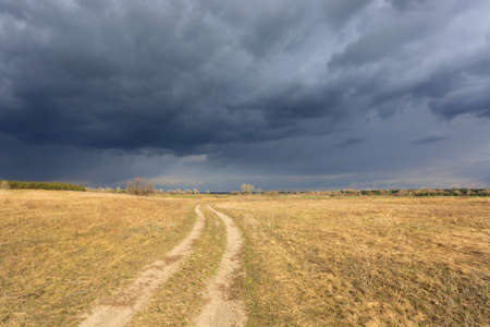 Dirt road across meadow with dry grass before spring thunderstorm