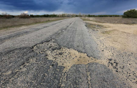 potholes on an old asphalt country road