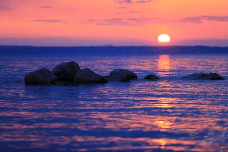 stones in lake water on sunset sky background Standard-Bild