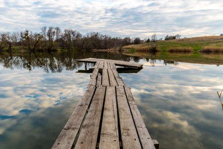 evening scene with wooden bridge on lake Standard-Bild