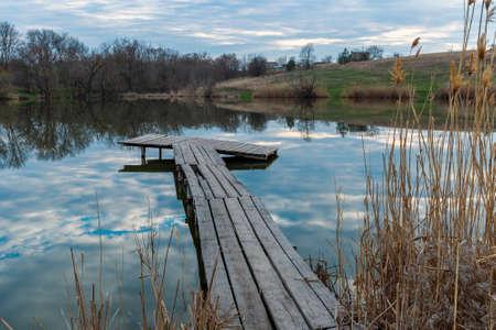 wooden firshing bridge on rural lake at evening time