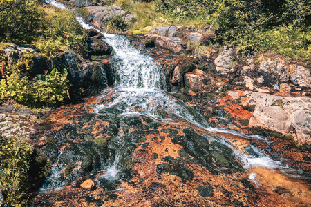 Mountain River Flow Through The Black And Orange Stones In The .. Stock Photo, Picture And Royalty Free Image