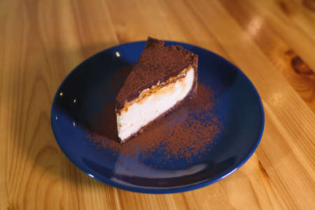 Chocolate cheesecake on a blue saucer on a large bright wooden table