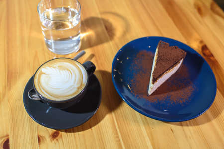 Chocolate cheesecake on a blue saucer, a glass of water and a cup of fresh cappuccino on a large bright wooden table