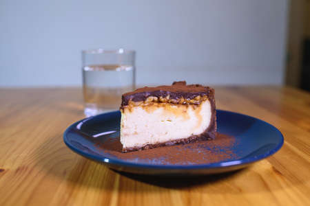Chocolate cheesecake on a blue saucer and a glass of water on a large bright wooden table