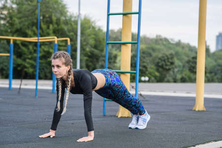 Sports girl doing exercises on the buttocks on the playground Stock Photo