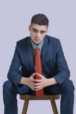 Portrait of a young boy in a suit with his arms crossed