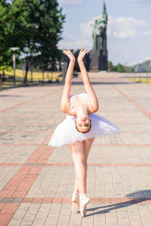 Young and beautiful ballerina posing on the street