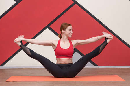 Athletic woman practicing healthy yoga exercises indoors