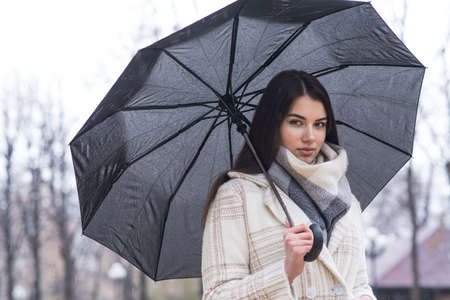 Portrait of a brunette girl with an umbrella walking in cloudy and rainy weather Imagens