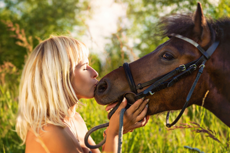 Portrait of blonde beautiful woman with a horse on nature