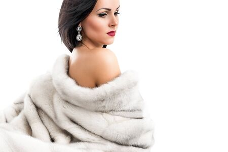 Portrait of a beautiful young woman in a mink coat on a white background