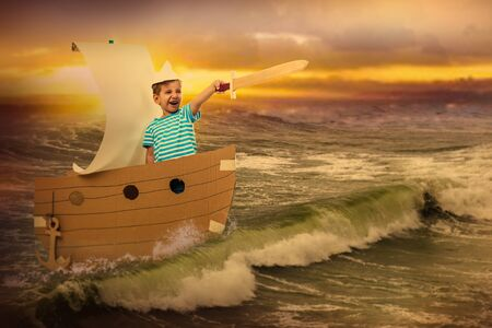 Little brave captain. Portrait of a child with a wooden sword. He floats in a cardboard boat on the sea Stock Photo
