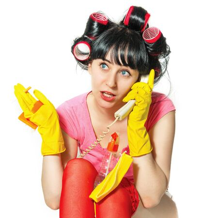 Portrait of a young woman in casual clothing, rubber gloves, hair curlers. She talks on the phone. In her hands the means for cleaning the house and a cigarette