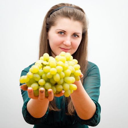Beautiful girl offers grapes