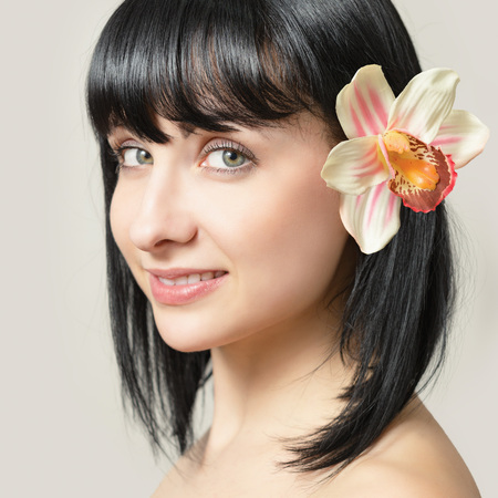 Portrait of a beautiful young woman with a flower in her hair