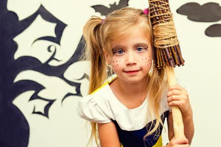 Halloween. Girl with a broom