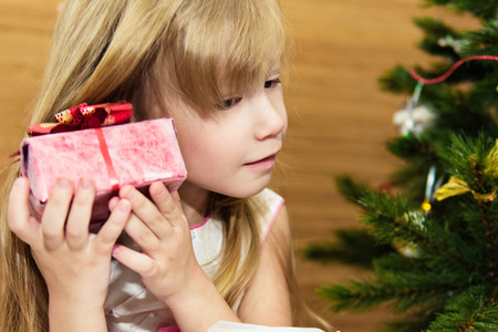 Girl with a gift in the Christmas tree