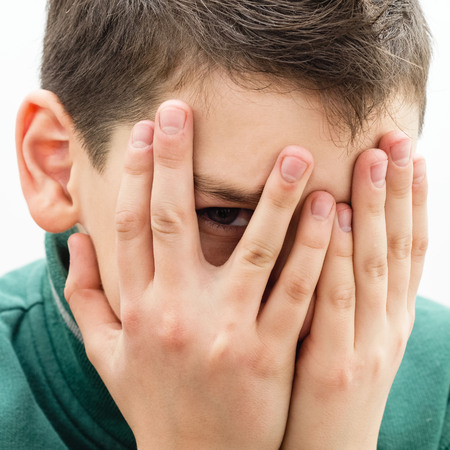 bashfulness: Teenager buried his face in his hands