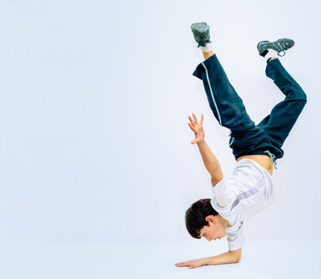 teeny: The dark-haired boy standing on his hand. He dances breakdance