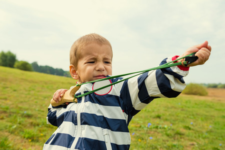 disobedience: A boy learns to shoot a slingshot
