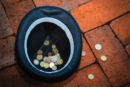 penury: Black hat with euro coins on a brick background