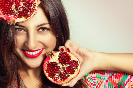 Portrait of a beautiful young woman with a pomegranate Stock Photo