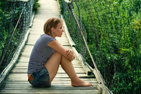 desolacion: Portrait of a sad girl on the bridge Foto de archivo