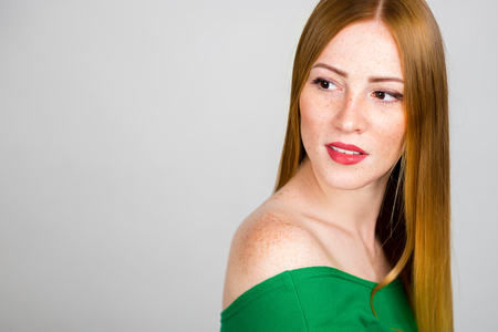 Porträt einer schönen jungen rothaarigen Frau . Lächelndes Mädchen auf einem grauen Hintergrund Standard-Bild