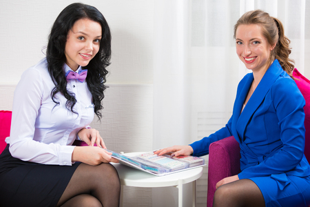 The beauty salon administrator communicates with the client. Portrait of two beautiful women