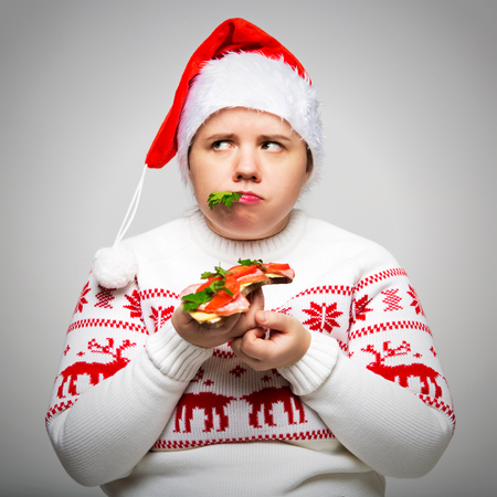 Portrait of a fat woman with a large sandwich in her hands. She is wearing a festive Christmas sweater and Santa hat. Overeating on holidays
