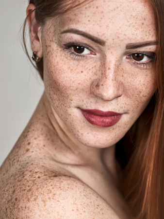 Portrait of a beautiful young red-haired woman. Female face closeup