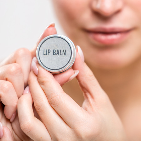 Lip balm. Cosmetic product in female hands. Close-up photo Archivio Fotografico