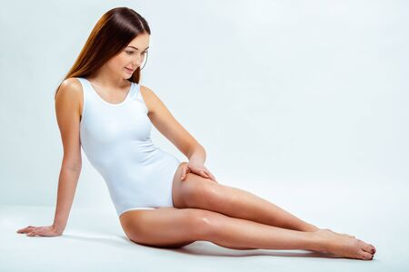 Portrait of a beautiful young woman with long slender legs. Depilation Stock Photo