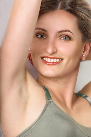 Portrait of a beautiful young woman smiling closeup. She shows a smooth armpit Фото со стока
