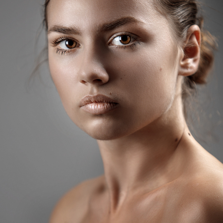 Portrait of a beautiful young woman close-up on gray background